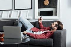 Le jeune homme heureux se trouve sur la musique de écoute de sofa avec des écouteurs Photographie stock