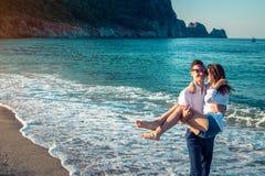 Le jeune homme heureux tient son amie dans des ses bras sur la plage tropicale Image stock