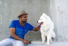 Le jeune homme indien regarde un grand chien blanc et garde une main sur la tête du ` s de chien Photo libre de droits