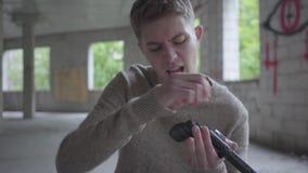 Le jeune homme insouciant charge le revolver chantant un plan rapproché de chanson Le type préparant pour tuer les balles de mise clips vidéos
