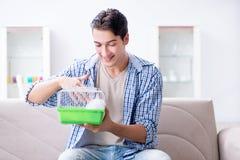 Le jeune homme jouant avec le lapin d'animal familier à la maison Photo stock