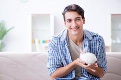 Le jeune homme jouant avec le lapin d'animal familier à la maison Photos stock