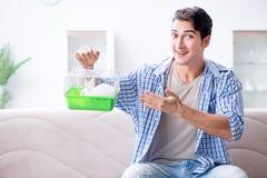 Le jeune homme jouant avec le lapin d'animal familier à la maison Photographie stock libre de droits