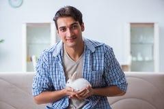 Le jeune homme jouant avec le lapin d'animal familier à la maison Image stock