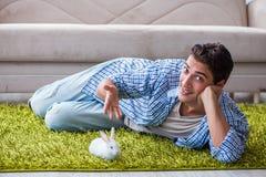Le jeune homme jouant avec le lapin d'animal familier à la maison Photos libres de droits