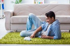 Le jeune homme jouant avec le lapin d'animal familier à la maison Photo libre de droits