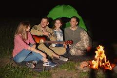 Le jeune homme jouant la guitare pour des amis s'approchent du feu Images stock