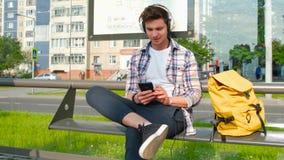 Le jeune homme joyeux attend le transport à l'arrêt d'autobus M?le s'asseyant sur le banc Le type à l'aide du smartphone écoute m clips vidéos