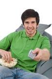 Le jeune homme jugeant à télécommande regardent la télévision photos libres de droits