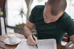 Le jeune homme lit le journal et observe les nouvelles offres d'emploi photographie stock