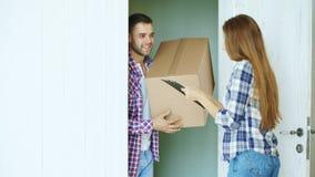 Le jeune homme livrent la boîte en carton au client à la maison Presse-papiers de connexion de femme pour recevoir le colis photo libre de droits