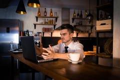 Le jeune homme mécontent s'assied dans la cuisine au compteur de barre et travaille dans l'ordinateur portable photographie stock