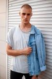 Le jeune homme modèle américain beau dans des jeans vêtx près d'un blanc image stock