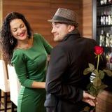 Le jeune homme modeste avec une rose et son amie. Rendez-vous en café Photographie stock libre de droits