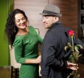 Le jeune homme modeste avec une rose et son amie. Rendez-vous en café Photos stock