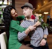 Le jeune homme modeste avec une rose et son amie. Rendez-vous en café Photos libres de droits