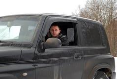 Le jeune homme monte pendant l'hiver la jeep sur la neige Photographie stock