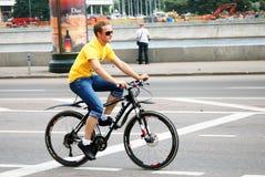 Le jeune homme monte un vélo Photo stock