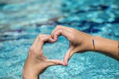 Le jeune homme montre le signe d'amour avec la forme de coeur constituée par des mains Images libres de droits