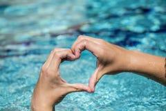 Le jeune homme montre le signe d'amour avec la forme de coeur constituée par des mains Photos libres de droits
