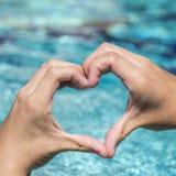 Le jeune homme montre le signe d'amour avec la forme de coeur constituée par des mains Photo libre de droits