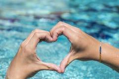 Le jeune homme montre le signe d'amour avec la forme de coeur constituée par des mains Photo stock