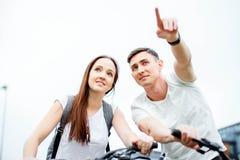 Le jeune homme montre son itinéraire d'amie Voyage de bicyclette Image stock