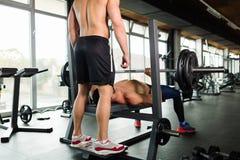Le jeune homme musculaire beau faisant le banc à presse et obtient l'aide photographie stock libre de droits
