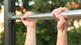 Le jeune homme musculaire faisant la traction se lève sur une barre en parc banque de vidéos