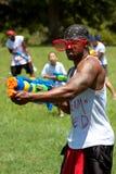 Le jeune homme musculaire injecte des gens avec le canon d'eau Images libres de droits