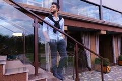 Le jeune homme musulman se tient dans le sourire intégral et la pose avec h Image libre de droits