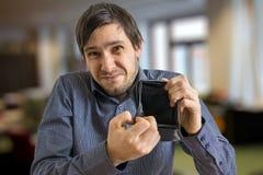 Le jeune homme n'a aucun american national standard d'argent montre son portefeuille vide photographie stock libre de droits