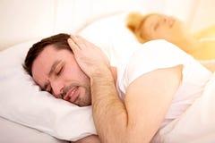 Le jeune homme ne peut pas dormir en raison de l'amie ronflant Images stock