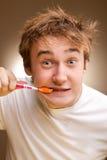 le jeune homme nettoie des dents Images stock
