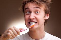 Le jeune homme nettoie des dents Photo stock