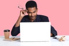 Le jeune homme noir d'affaires avec l'ordinateur portable, s'assied à la table blanche, tient ses lunettes à disposition, a des e images stock