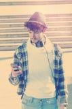 Le jeune homme observant le téléphone intelligent dans la rue a appliqué l'inst de filtre Photo stock