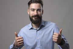 Le jeune homme occasionnel futé barbu heureux avec du charme montrant des pouces lèvent le geste de main souriant à l'appareil-ph Photo stock