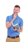 Le jeune homme occasionnel tient le livre et sourit d'un air songeur Image stock
