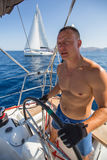 Le jeune homme oriente le bateau de yacht de navigation pendant la régate luxe Images stock