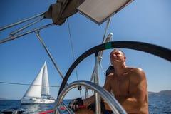 Le jeune homme oriente un bateau à voile à la régate de yacht Image libre de droits