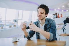 Le jeune homme ou indépendant attrayant s'assied en café et emploie son mobile Photographie stock libre de droits