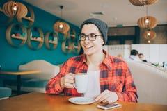 Le jeune homme ou l'indépendant attirant s'assied dans le café et le thé potable Photo libre de droits