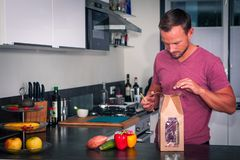 Le jeune homme ouvre un paquet des ingrédients frais pour faire un dîner sain photo libre de droits