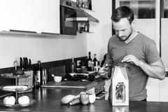 Le jeune homme ouvre un paquet des ingrédients frais pour faire un dîner sain image stock