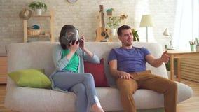 Le jeune homme a pété se reposant sur le divan à côté d'une jeune femme qui a porté un respirateur de l'odeur banque de vidéos