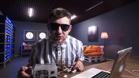 Le jeune homme parle à la caméra ayant la boîte d'alimentation d'énergie avec le refroidisseur mis sur le bureau banque de vidéos