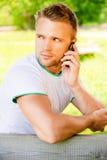 Le jeune homme parle du téléphone Image libre de droits