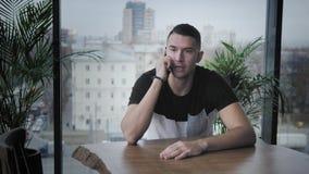 Le jeune homme parlent par le téléphone Travail d'ind?pendant sur le netbook dans coworking moderne Programmeur au travail ? dist banque de vidéos