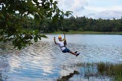 Le jeune homme passe par une lagune sur la ligne de fermeture éclair en Chiang Mai photos libres de droits